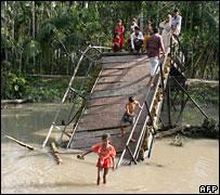 Villagers cross a collapsed bridge in Bashbariya in southern Bangladesh 17 November 2007