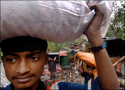 Bangladeshis carry their belongings in the village of Kanainagar, Bangladesh, 16 November 2007