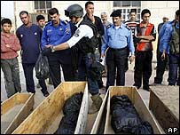An Iraqi policeman puts a bag with human remains in a coffin in Baghdad