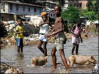 Children play in a stream used as a toilet in the Freetown slum of Kroo Bay