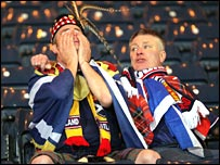 Scotland fans console each other after their country's defeat by Italy