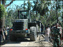 Army tractor moving fallen trees