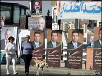 Two women walk past election posters in Amman