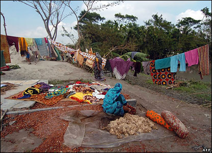 A women dries clothes in a village in Rupsha