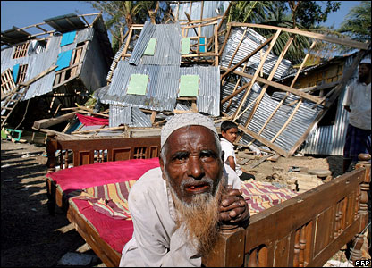 A cyclone affected elderly man rests on a bed near a devastated house in Choto Taltoli village, on the southern coastal area of Bangladesh