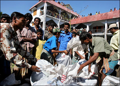 Bangladeshi cyclone affected people wait as aid workers unload relief goods in Porir Khal village