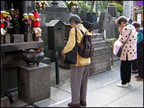 Pensioners praying at a temple in Tokyo