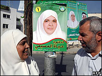 Hayat Mseimi, a candidate of the Islamic Action front (IAF), speaks with her husband in front of her electoral poster in Zarqa