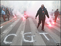 Striking French rail workers block a road