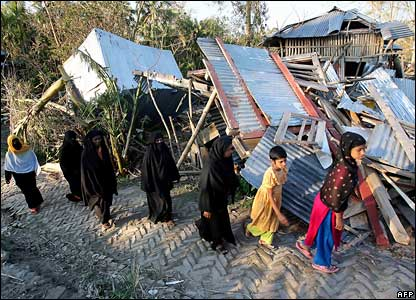 Bangladeshi cyclone affected women and children walk past devastated houses in Chalabangha village, on the southern coastal area of Bangladesh