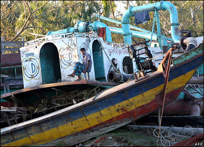 A Bangladeshi cyclone affected man sits on a passenger ferry which was thrown off the river by cyclone in Chalabangha village, on the southern coastal area of Bangladesh,