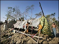 A family stands by their makeshift shelter