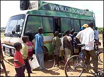 Tour bus promoting the Commonwealth summit in Kampala is surrounded by people in the northern town of Gulu