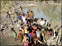 Children gather on the edge of the river to wait for aid supplies