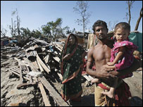 A family stands by the wreckage of their shelter along the riverbank