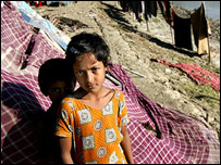 A small girl and her brother stand by their makeshift home on the river bank