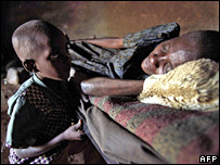 A Kenyan lady suffering from HIV/Aids lies on her bed with her son besides her (28 November 2003)