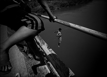 Children jumping from bridge by Greg Funnell