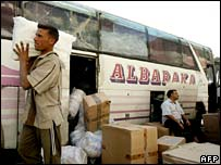 An Iraqi worker unloads cardboard boxes from a bus carrying Iraqi returnees to Baghdad's international bus station on 9 November