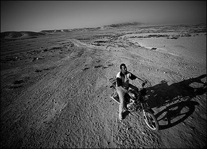 Man on motorbike in desert by Greg Funnell