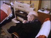 Elderly man by a fire