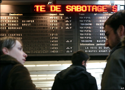 "Travellers look at an electronic board at the Montparnasse train station in Paris reporting ""sabotage"""