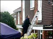 A police officer searches the front of the house