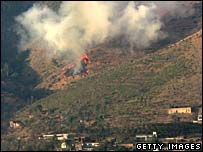 A fire burns after Pakistani forces shelled a suspected militant position near Fizagat, Swat valley, 20 November
