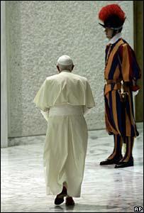 Pope Benedict XVI walks past a Vatican Swiss Guard. File photo