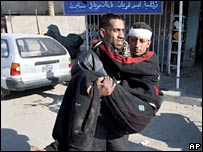 A injured man is carried to hospital after the Ghazil pet market bombing in Baghdad on 23 November 2007.