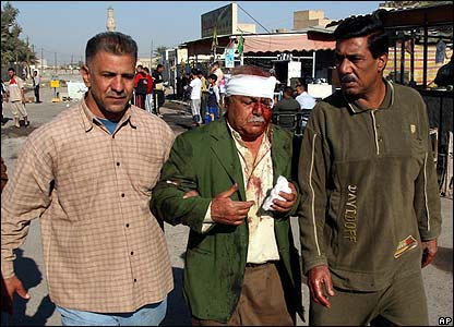 A wounded man is helped away from the Ghazil market in Baghdad