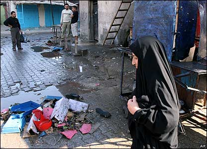A woman crosses Ghazil market after the blast