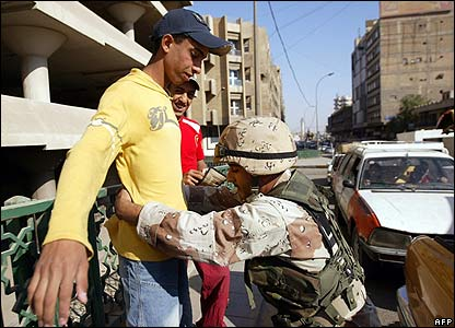 An Iraqi Army soldier checks a passer-by near Ghazil market after the attack