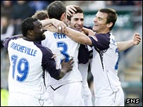 Carlos Cuellar is mobbed by teammates after opening the scoring for Rangers