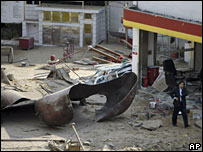A man walks past debris after a blast at a gas station near Shanghai, 24 November 2007