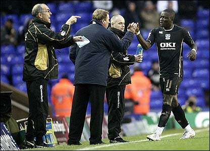 Portsmouth's Sulley Muntari celebrates with his boss Harry Redknapp