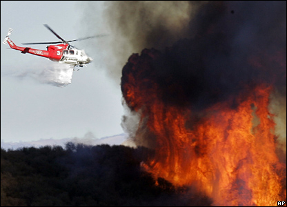 An emergency helicopter drops water on the fire