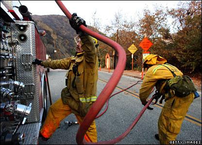 Malibu Firefighters load a fire hose back onto a fire engine