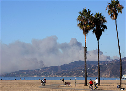 The Malibu hills covered in a huge pall of smoke, seen from a distance