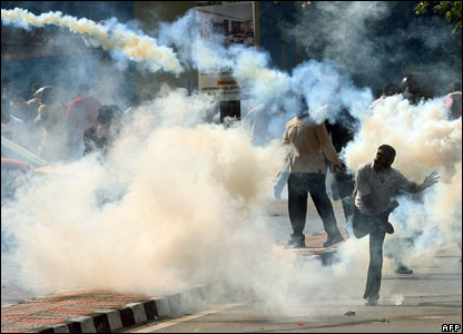 A protester throws a tear gas canister back at police