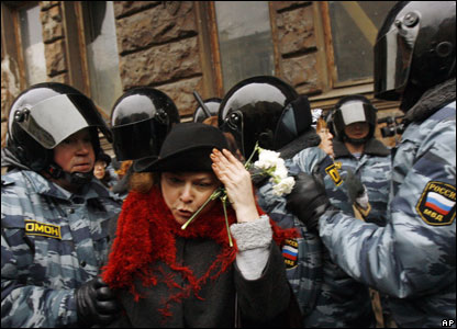 A protester holding a white flower is surrounded by riot police