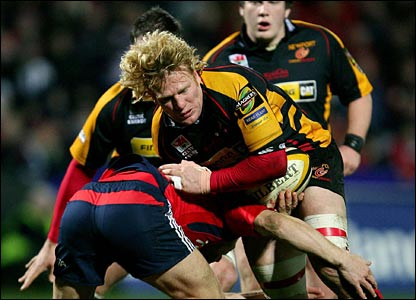Jamie Ringer gets tackled by Paul Warwick as the Dragons crash to a heavy defeat in Munster