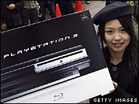 Employee in Japanese shop holding Playstation 3 console