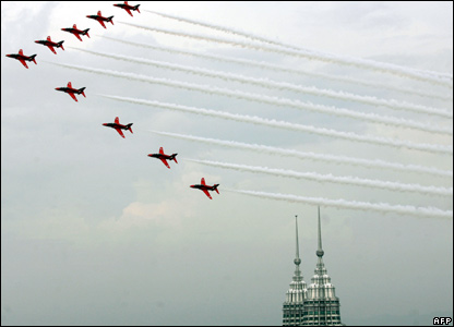 The Royal British Air Force Red Arrows aerobatic team fly over Malaysia's Petronas twin towers as they arrive in Kuala Lumpur