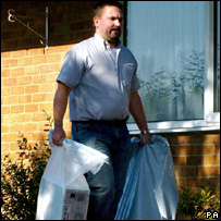 A police officer takes a computer from Kieren Fallon's home