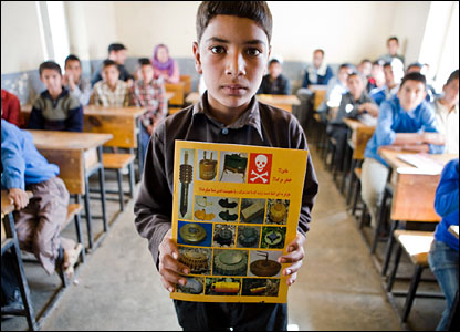 Afghan schoolboy with mine information sheet