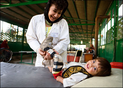 An Afghan physiotherapist with a child patient