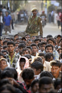 A soldier stands guard over tribal protestors in Assam