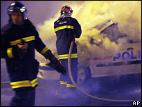 Firemen try to extinguish a fire in a police car in Villiers-le-Bel