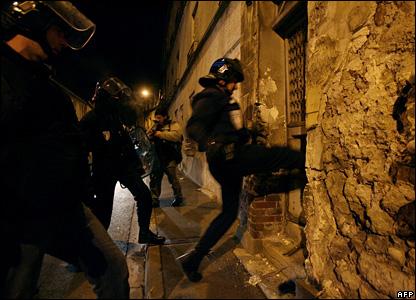 Riot police kick in a door in Villiers-le-Bel